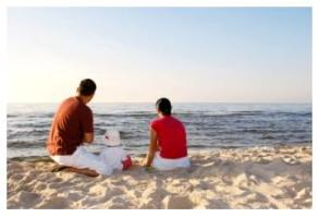 Couple with small child on beach looking out over the water