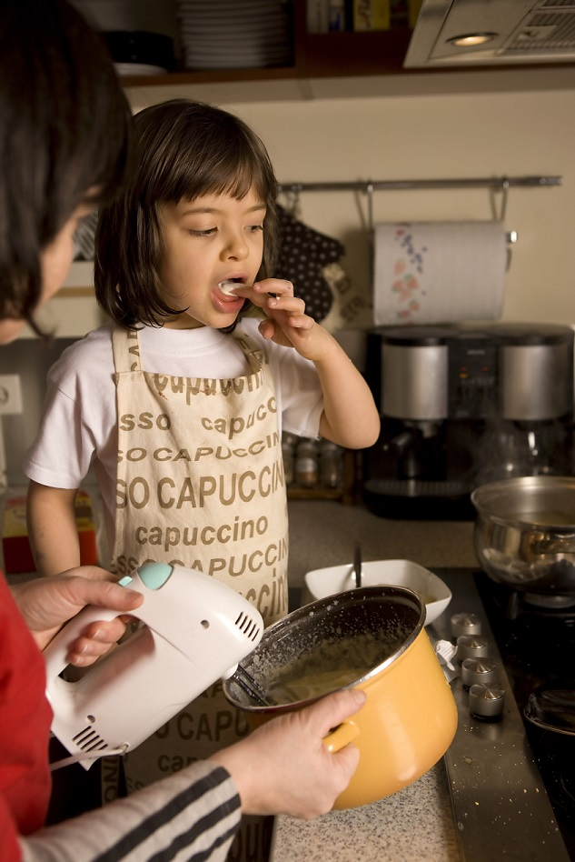 happy homeschooled child baking at home with mother