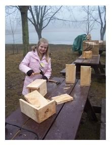 Child outdoors making a birdhouse at Springwater Conservation Area, Orwell, Ontario