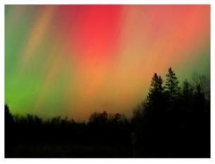Northern lights glowing red in the northern sky