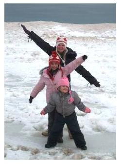 Three Children playing in the snow in winter on the beach at Port Stanley, Ontario, Canada