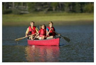 family canoeing in an Ontario lake in red canoe