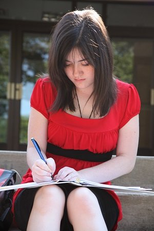 Homeschool girl in red dress sitting outside in the warm weather, doing her school work